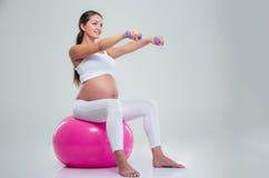 Женщина делая тренировки с гантелями на шарике фитнеса Стоковое Изображение