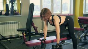 Женщина делая тренировки для задней части используя гантели отдыхая на колене и руке сток-видео