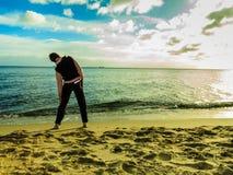 Женщина делая тренировку фитнеса на пляже на заходе солнца Стоковые Фото
