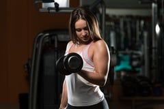 Женщина делая тяжеловесную тренировку для бицепса Стоковое фото RF