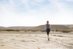 Женщина делая фитнес утра, который побежали в пустыне стоковое изображение rf