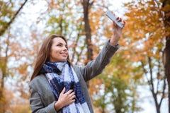 Женщина делая фото selfie в парке осени Стоковые Фотографии RF