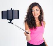 Женщина делая фото selfie на smartphone с ручкой Стоковая Фотография