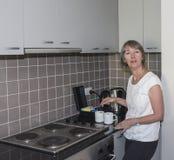 Женщина делая чашки чаю стоковая фотография