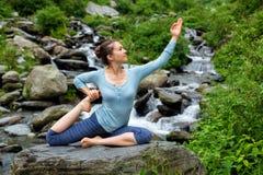 Женщина делая asana йоги на тропическом водопаде Стоковое Фото