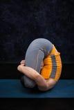Женщина делая pindas Garbha asana йоги Ashtanga Vinyasa йоги Hatha Стоковое Изображение RF