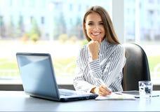 Женщина дела работая на портативном компьютере