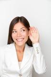 Женщина дела слушая с рукой к принципиальной схеме уха стоковые изображения rf