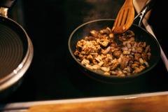 Женщина жарит грибы и морковей Варочный процесс Стоковое Изображение RF