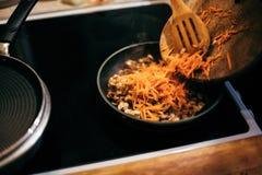 Женщина жарит грибы и морковей Варочный процесс Стоковая Фотография RF