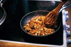 Женщина жарит грибы и морковей Варочный процесс Стоковые Изображения RF