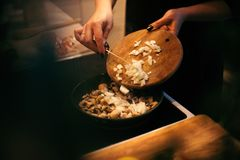 Женщина жарит грибы и морковей Варочный процесс Стоковое Изображение