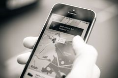 Женщина ждать автомобиль uber на улице держа smartphone стоковое изображение