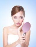 Женщина заботы кожи смотря себя с зеркалом Стоковые Фотографии RF