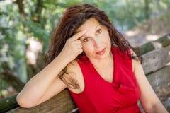 Женщина заботливо сидя на скамейке в парке Стоковое Изображение RF
