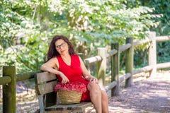 Женщина заботливо сидя на скамейке в парке Стоковое Фото