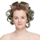 Женщина завивая ее волос с роликом Стоковые Фотографии RF