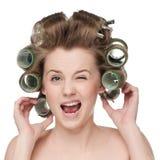Женщина завивая ее волос с роликом Стоковые Изображения RF