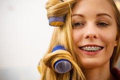 Женщина завивая ее волосы используя ролики Стоковое Изображение