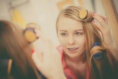 Женщина завивая ее волосы используя ролики Стоковая Фотография RF