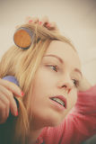 Женщина завивая ее волосы используя ролики Стоковые Фотографии RF