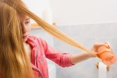 Женщина завивая ее волосы используя ролики Стоковые Фото