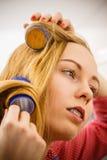 Женщина завивая ее волосы используя ролики Стоковые Изображения RF