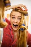 Женщина завивая ее волосы используя ролики Стоковые Изображения