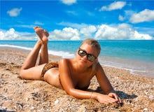 Женщина загорает на пляже Стоковые Изображения