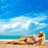 Женщина загорает на пляже Стоковая Фотография