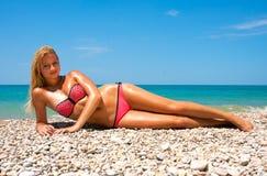 Женщина загорает на пляже Стоковые Фото