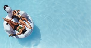 Женщина загорая на плавая игрушке бассейна раздувной Стоковая Фотография