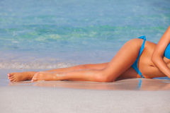 Женщина загорая на пляже на летних каникулах стоковое изображение