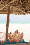 Женщина загорая на тропическом пляже Стоковое Изображение