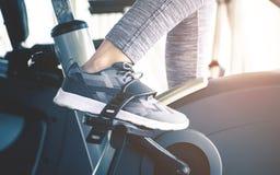 Женщина задействует на машине велосипеда фитнеса закручивая Стоковые Фото