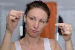 Женщина задерживая 2 тампона, одного большого, одного малого Стоковое Изображение