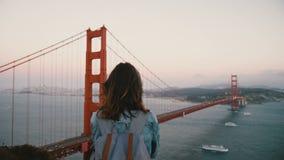Женщина заднего взгляда молодая счастливая мирная туристская с рюкзаком и ветром в ее волосах наблюдая иконический взгляд моста з сток-видео