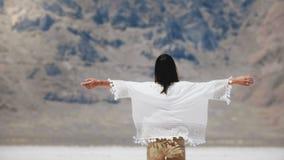 Женщина заднего взгляда молодая счастливая свободная местная идя к эпичной горе поднимая оружия на озере пустыни соли, концепцию  видеоматериал
