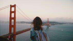 Женщина заднего взгляда молодая счастливая туристская с рюкзаком наслаждаясь сильным ветером в ее волосах на иконическом взгляде  видеоматериал