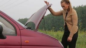 Женщина закрывает клобук автомобиля сток-видео
