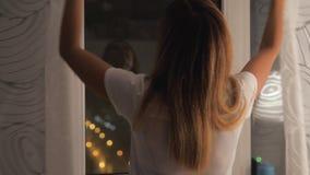 Женщина закрывает окно и занавесы перед идти спать дома сток-видео