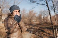 Женщина замерла в парке Нагревает дыхание рук стоковые фото