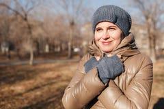 Женщина замерла в парке осени Я пересек обе руки о a стоковое изображение