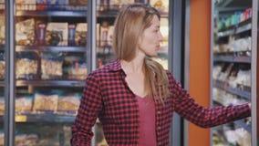 Женщина заметила привлекательный контейнер с мясом и принимать сладкий выбор от полки в магазине супермаркета акции видеоматериалы