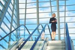 Женщина записывает o-nline автомобиль, пока стоит в авиапорте около moving лестницы Стоковая Фотография RF