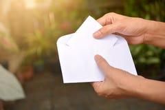 Женщина заполняет насмешку белой бумаги вверх в почту конверта Стоковая Фотография