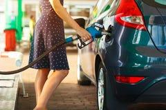Женщина заполняет нефть в ее автомобиль стоковое изображение