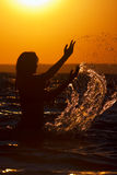 женщина захода солнца выплеска силуэта Стоковая Фотография