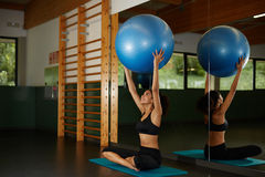 женщина задерживая шарик Pilates и сидя на циновке во время ее тренировки фитнеса в спортзале Стоковые Изображения RF