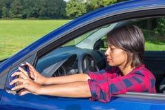 Женщина за рулевым колесом регулируя зеркало автомобиля Стоковая Фотография
